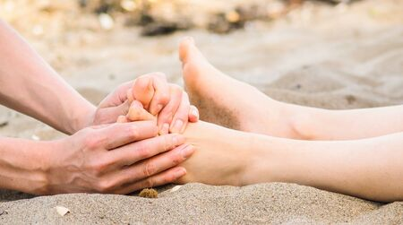 outdoor lighting: Foot massage on a beach in sand, male and female caucasian