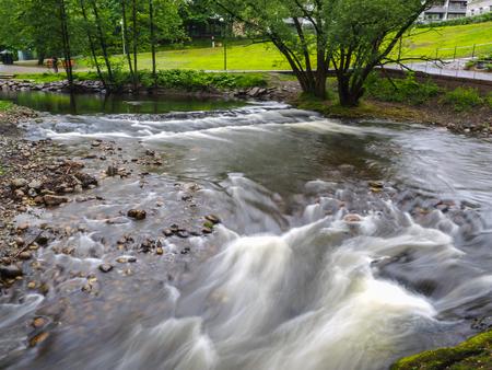 Strong current in river passing around rocks with long exposure Lizenzfreie Bilder