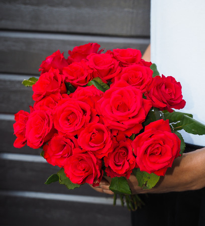 Male person holding a beautiful bouquet of red roses wearing white shirt and black pants against a gray wooden wall