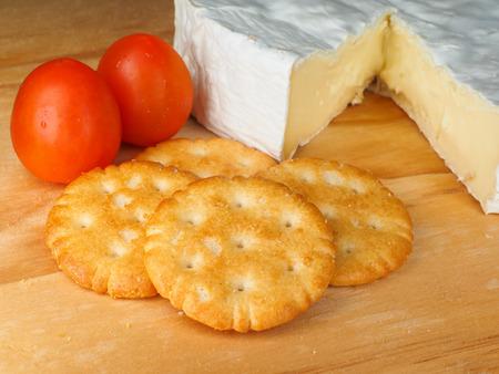 Traditioneller weicher weißer Käse mit Tomaten und Keksen auf einem Holzbrett
