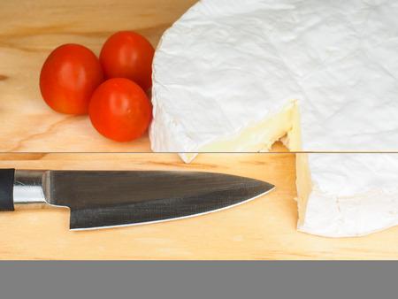 Traditioneller weicher weißer Käse mit Tomate und Messer auf einem Holzbrett