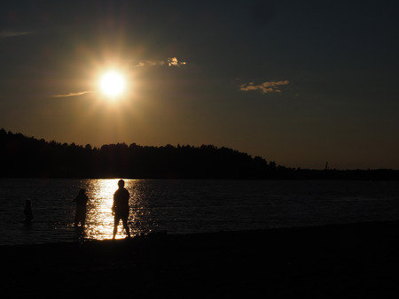 Silhouette of people bathing under late summer sun on a beach