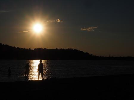 Schattenbild von den Leuten, die unter Spätsommersonne auf einem Strand baden Lizenzfreie Bilder