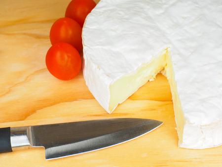 Camembertkäse mit Messer und kleinen roten Tomaten an der Seite auf Holzbrett