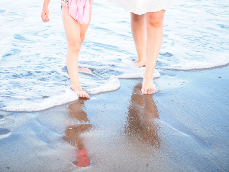 Mother and daughter walking in spuming sea water foam on a beach