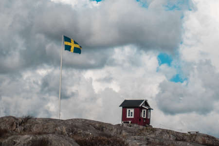 A classic red hut in Sweden next to a Swedish flag Stock Photo
