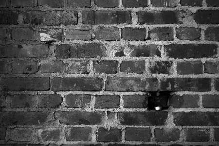 Una vela en un agujero en una hermosa pared de ladrillos en blanco y negro