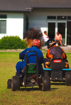 A couple of drivers participating in a lawnmower race Stock Photo