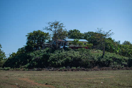 A simple rural house on a green hill with trees by a grass field in Ngwesaung, Irrawaddy, western Myanmar