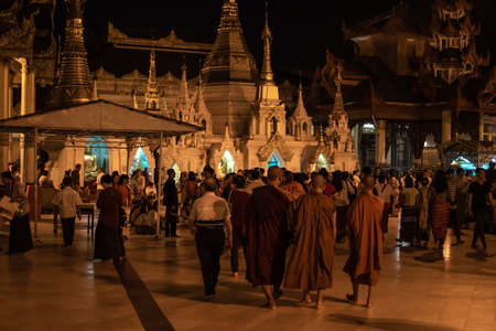 Yangon, Myanmar - December 30, 2019: Three monks and visitors walks around the Shwedagon Pagoda and its surrounding golden structures at night
