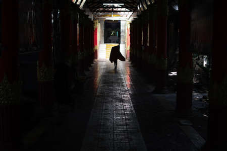 YANGON, MYANMAR - JANUARY 1 2020: A silhouette of a young monk who fixes the robe while walking down a dark walkway with pillars into the light