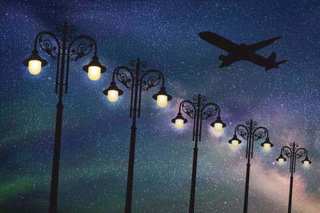 Flying aircraft and vintage lampposts at night. Vector illustration with silhouette of passenger airplane under starry sky 矢量图像