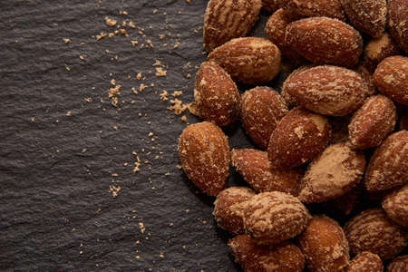 salted: nuts, salted almonds, on a dark background