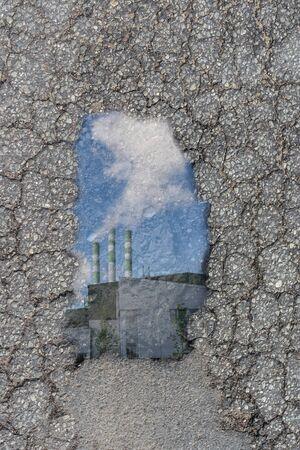 Ein Schlagloch in der Straße. Ein Loch im Boden. Mit Fabriksilhouette und Schornstein mit Rauch in einem blauen Himmel.