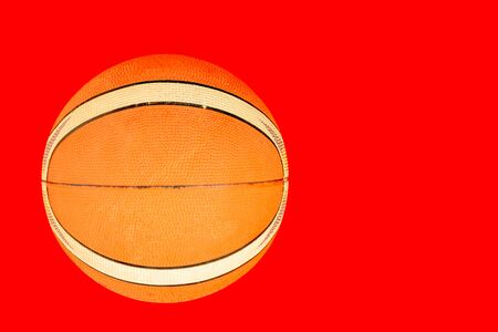 A old basket ball isolated with a red background