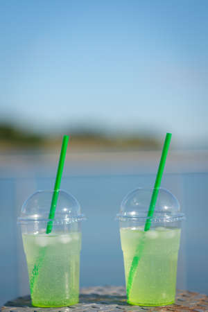 Medium shot of a glass filled to the top green drinking liquid, green straws with ice cubes with blurred blue ocean and sky in the distance