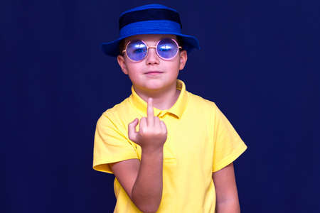 Attractive young caucasian schoolboy with hat sunglasses and yellow t shirt shows middle finger.Close up concept.Studio blue wall.
