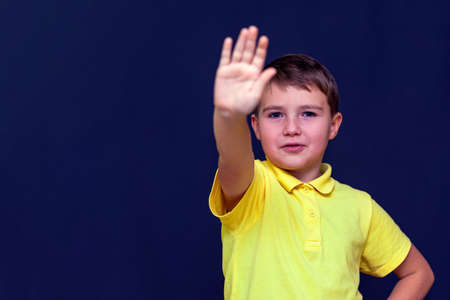 Little 9s boy putting his hand out making stop sign gesture.Blue studio background.