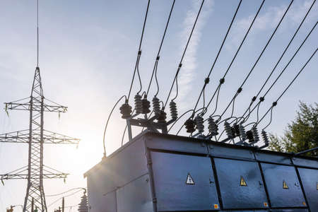 Electric power transmission lines in the evening. High voltage switchgear and equipment of power plant. Stock Photo