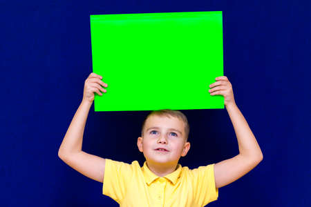 Happy nice calm caucasian child boy keep advertising above his head a poster for your information on the blue background