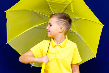 Side view Attractive caucasian blond schoolboy with umbrella on blue studio background.Boy shows all kinds of grimaces. Archivio Fotografico