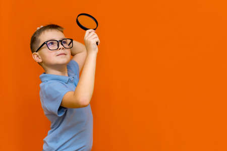 Beautiful european young boy with glasses holding and looking through magnifying glass.Orange studio wall.