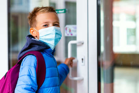 Young schoolboy wearing protective mask is trying to open the school door. Behind the backpack Schoolboy look at camera