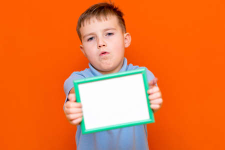 Portrait of caucasian schoolboy in t-shirt posing isolated on orange background. Mock up copy space. Shows advertising protruding forward white empty blank billboard with place for text or image.