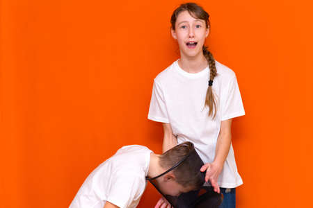 Friendship Concept.Caucasian young boy and girl wearing white t shirts playing with dark trash bin.The boy holds his head in the trash.Orange isolated studio background.