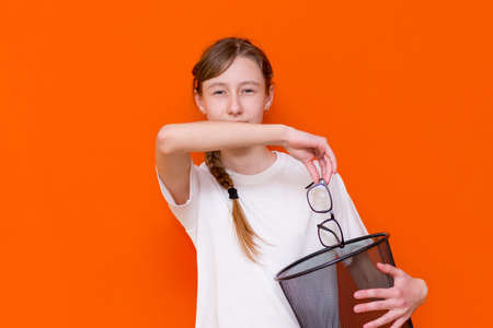 Close up smiling calm serious young girl throw away her glasses in the trash bin