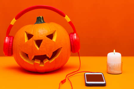 Happy carved pumpkin Halloween decorations festival and music concept background.Mix variety candle items and pumpkin listening radio by headphone on orange background.