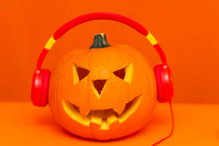 Happy Halloween decorations festival and music concept background.Mix variety candle items and pumpkin listening radio by headphone on orange background.