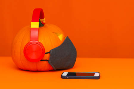 Side view Happy Halloween decorations festival and music concept background.Mix variety candle items face mask and pumpkin listening radio by headphone on orange background.