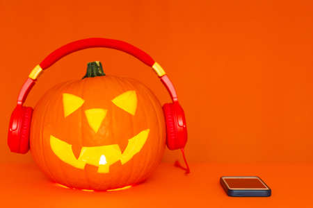 Happy carved pumpkin Halloween decorations festival and music concept background.Mix variety pumpkin listening radio by headphone on orange background.