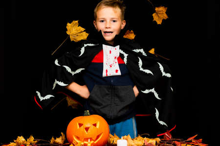 smiling face Young boy costume dressed as a halloween cosplay of scary dacula a jack'o pumpkin lantern on black yellow leaves background.Studio shot.