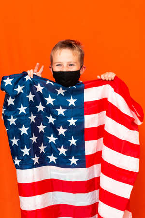 Attractive little boy with the flag of the United States, showing victory on a orange trendy background