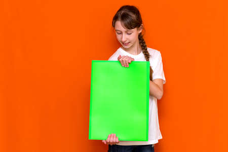 Calm caucasian young girl holding a bright green folder with a banner advertisement on a orange studio background. advertising copy space
