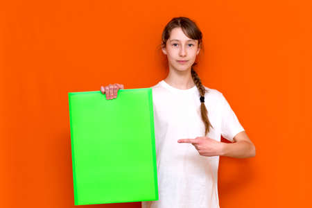 Surprised caucasian young long haired girl holding and poke at bright green folder with a banner advertisement on a orange studio background. copy space banner