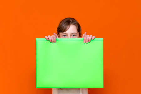 Mysterious caucasian young girl hiding under a bright green folder with a banner advertisement on a orange studio background. advertising copy space