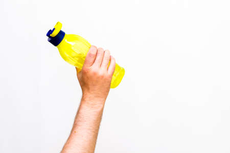 Close up image.Man's hand holds yellow bottle of water, isolated on white background.