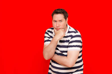 Middle age american man wearing navy striped t-shirt over isolated red background with hand on chin thinking about question 스톡 콘텐츠