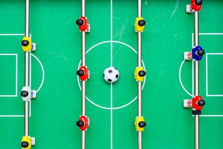 Top view table soccer with red yellow players and a ball.