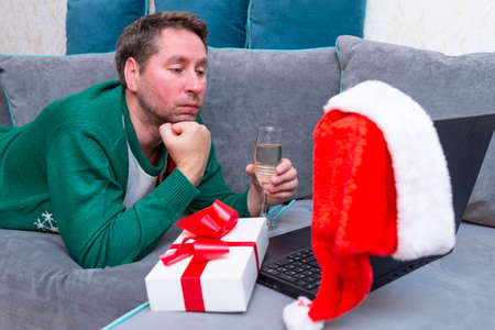 Caucasian alone male having video call. using laptop and toasting with Champagne while celebrating Christmas holyday.