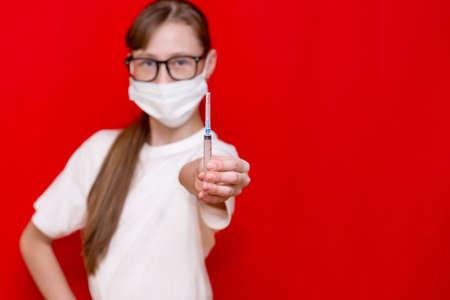 Teenage girl coronavirus medical mask with a syringe in his hands.Studio shot.