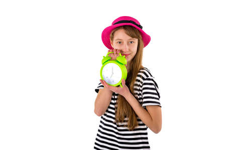 Teen Girl holding alarm Clock, isolated on white background. Portrait of caucasian teenager showing green alarm clock.Copy space.