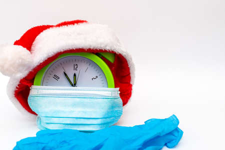 New Year alarm clock santa hat medical mask rubber gloves on white background countdown to midnight.Clock showing nearly 12.Copy space.