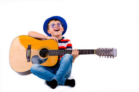 A boy kid plays guitar on a white background in the studio. Фото со стока