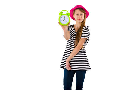 Teen Girl holding alarm Clock, isolated on white background. Portrait of caucasian teenager showing green alarm clock.