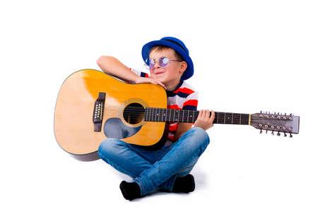 A boy kid holding guitar on a white background in the studio. Standard-Bild