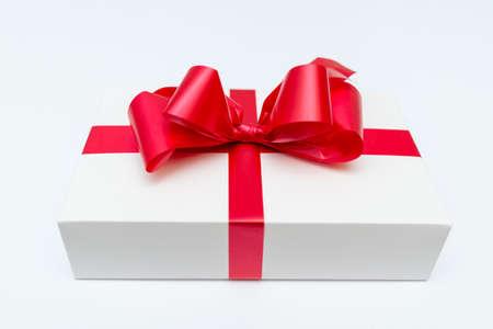 Cristmas white gift box present red bow white studio background.